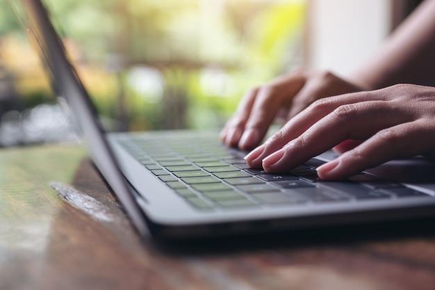 Immagine del primo piano delle mani facendo uso e digitando sulla tastiera del computer portatile sulla tavola di legno