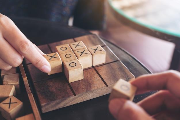 Immagine del primo piano di persone che giocano in legno tic tac toe gioco o gioco ox