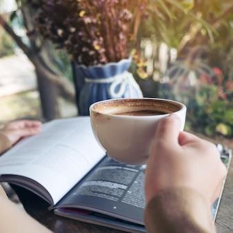 Immagine del primo piano di un libro di lettura della donna e di un caffè bevente in caffè