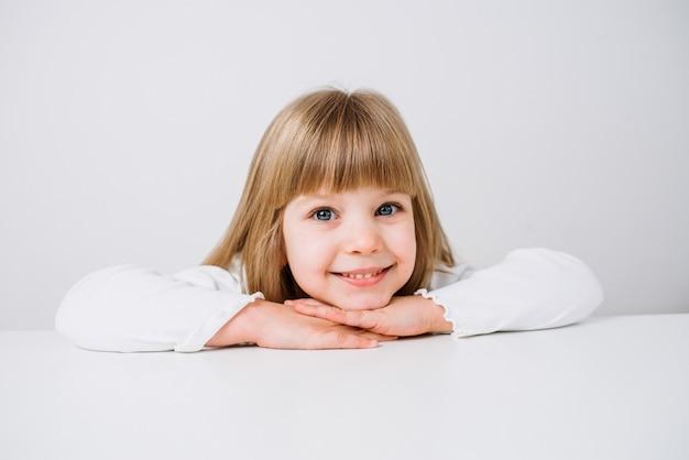 Immagine del primo piano di una bambina sorridente che si appoggia con le braccia attraversate