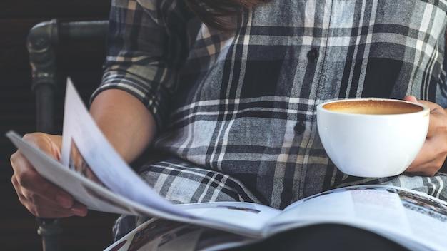 Immagine del primo piano di una donna che legge un libro mentre bevono caffè in caffè moderno