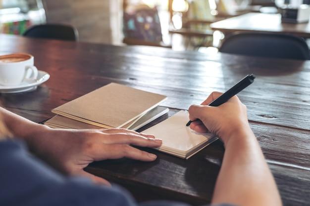 Immagine del primo piano di una donna che scrive su un taccuino in bianco con la tazza di caffè