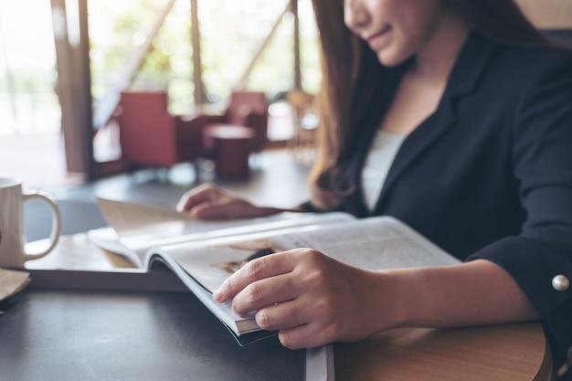 Immagine del primo piano di una donna di affari asiatica che legge un libro con la tazza di caffè sulla tavola in caffè