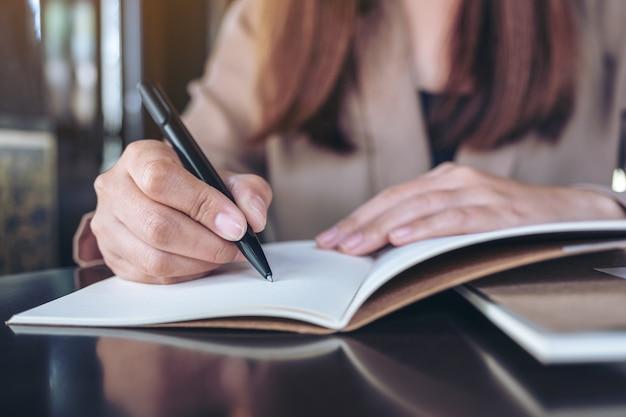 Immagine del primo piano di una donna di affari che scrive sul taccuino in bianco sulla tavola di legno