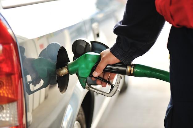 Immagine del primo piano di una mano degli uomini che riempie l'automobile di una pompa di benzina