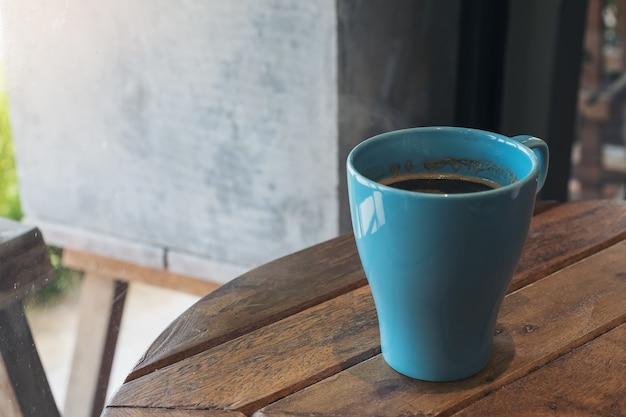 Immagine del primo piano di una tazza blu di caffè caldo sulla tavola di legno dell'annata in caffè