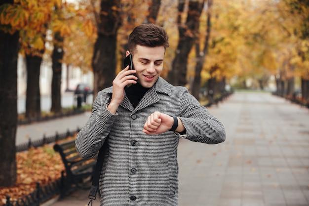 Immagine del riuscito uomo d'affari che parla sul cellulare, mentre continuando a incontrarsi in tempo