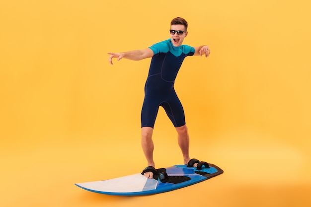 Immagine del surfista felice in muta e occhiali da sole usando la tavola da surf come sull'onda