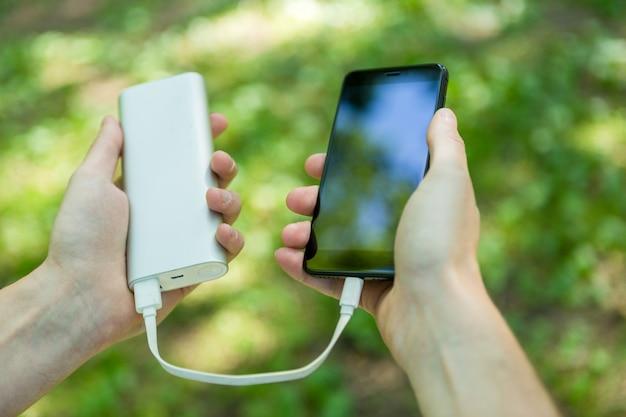 Immagine del telefono e del powerbank della tenuta dell'uomo