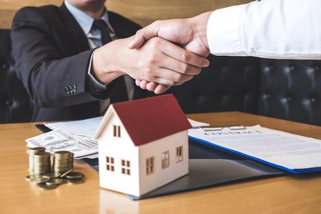 Immagine dell'affare riuscito di proprietà immobiliari, broker e clienti si stringono la mano dopo aver firmato il modulo di domanda approvato dal contratto, relativo all'offerta di mutuo ipotecario e all'assicurazione sulla casa