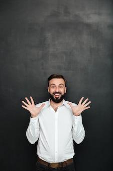 Immagine dell'impiegato di concetto maschio che gesturing sulla macchina fotografica con le mani su, essendo allegro sopra grigio scuro