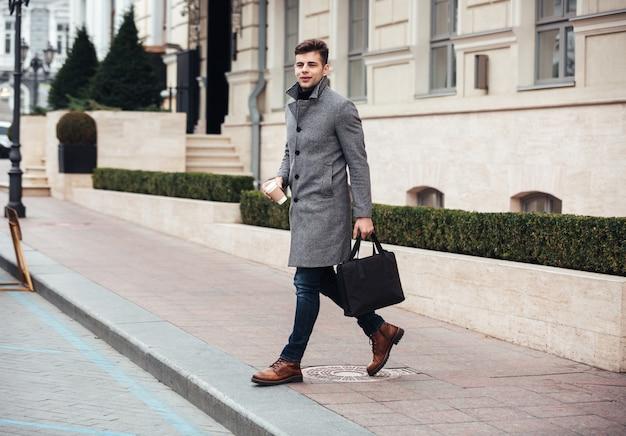Immagine dell'uomo d'affari bello con caffè asportabile a disposizione, attraversando la strada durante il giorno soleggiato