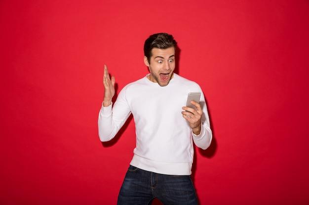 Immagine dell'uomo di grido colpito in maglione che esamina smatphone sopra la parete rossa