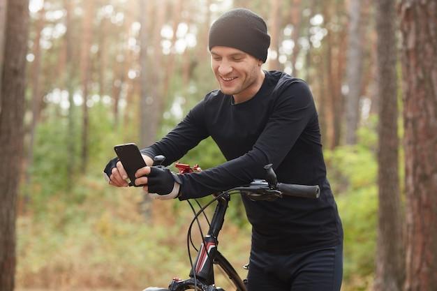 Immagine dell'uomo felice felice che posa nella foresta da solo con la bicicletta