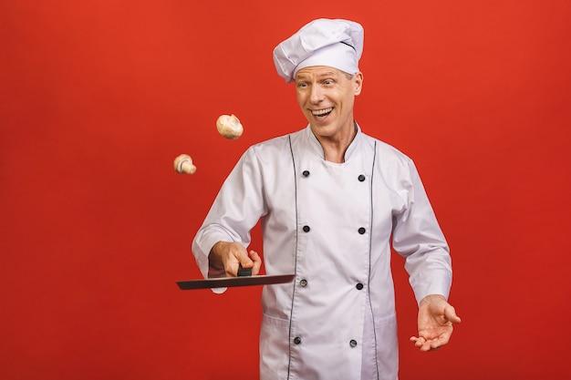 Immagine dell'uomo senior senior allegro in uniforme del cuoco che sorride e che tiene padella e funghi isolati sopra il fondo rosso della parete.