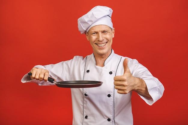 Immagine dell'uomo senior senior allegro in uniforme del cuoco che sorride e che tiene padella isolata sopra il fondo rosso della parete. pollice su.