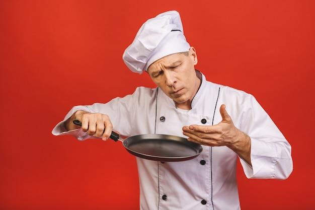 Immagine dell'uomo senior senior allegro in uniforme del cuoco che sorride e che tiene padella isolata sopra il fondo rosso della parete.