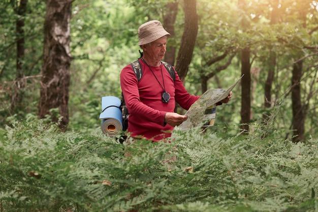 Immagine dell'uomo viaggiatore alla ricerca della giusta direzione sulla mappa, come viaggiare lungo la natura. vecchio turista con zaino in piedi nella foresta incredibile
