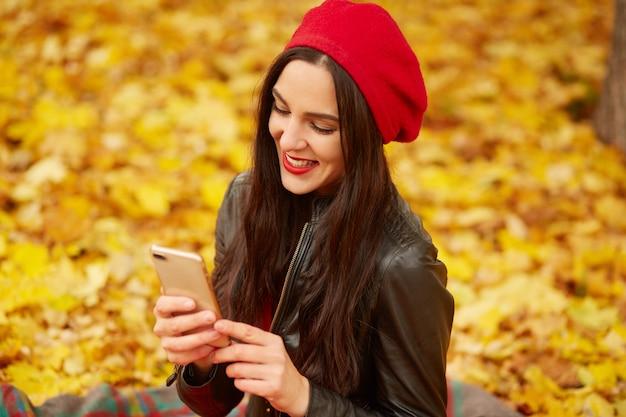 Immagine della bella donna caucasica bruna abiti berretto rosso e giacca di pelle nera, camminando attraverso il parco, smartphone femminile della holding
