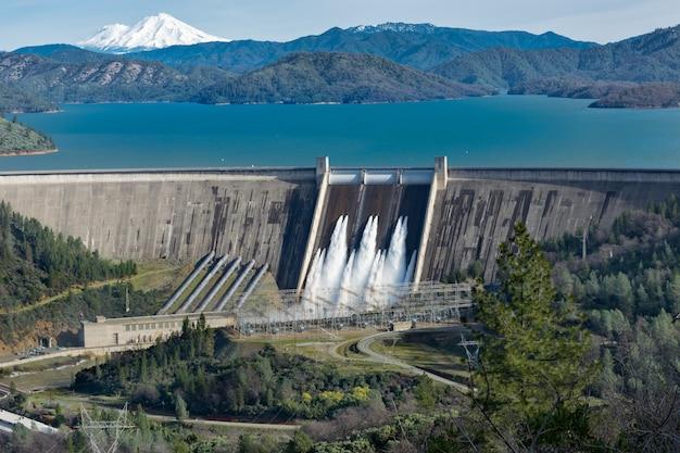 Immagine della diga di shasta circondata da strade e alberi con un lago e montagne