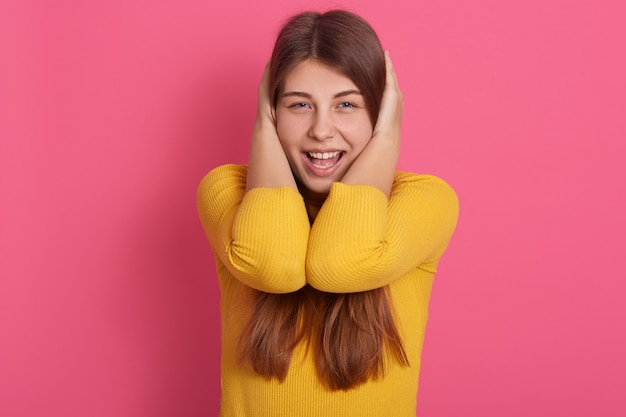 Immagine della divertente apertura adorabile giovane femmina apertura bocca ampiamente, coprendosi le orecchie con le mani, urlando, evitando rumori forti, indossando la felpa gialla. concetto di emozioni.