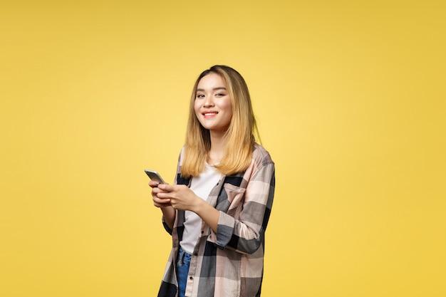 Immagine della donna asiatica soddisfatta con capelli lunghi che sorride e che manda un sms sul telefono cellulare