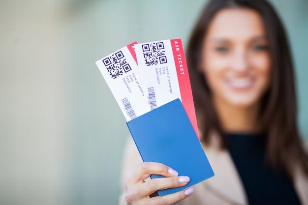 Immagine della donna europea che ha bei capelli marroni che sorridono mentre tiene i biglietti del passaporto e dell'aria