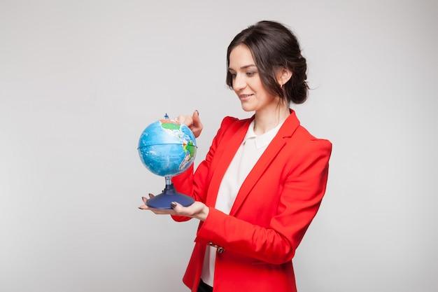 Immagine della donna graziosa in giacca sportiva rossa con la sfera della terra in mani