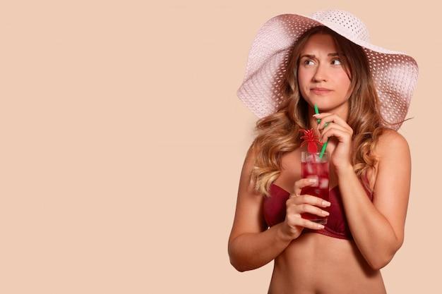 Immagine della femmina attraente turbata che ha espressione facciale sgradevole, guardando da parte, essendo in vacanza, tenendo il cocktail, trascorrendo il tempo da solo, avendo lunghi capelli biondi. copia spazio per pubblicità.