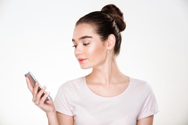 Immagine della femmina con capelli marroni in panino che chiacchiera o che legge libro elettronico facendo uso dello smartphone