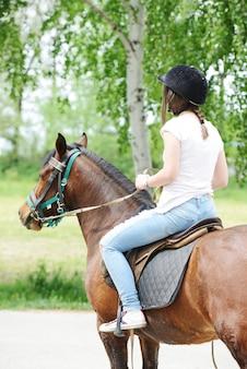 Immagine della femmina felice che si siede sul cavallo all'azienda agricola del villaggio