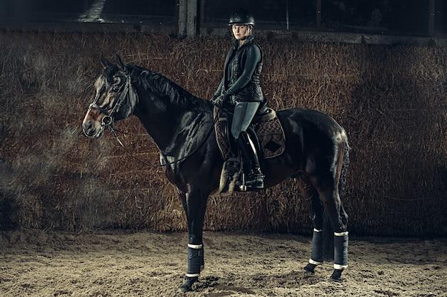 Immagine della femmina felice che si siede sul cavallo di razza