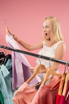 Immagine della femmina graziosa che osserva un vestito mentre scegliendolo.