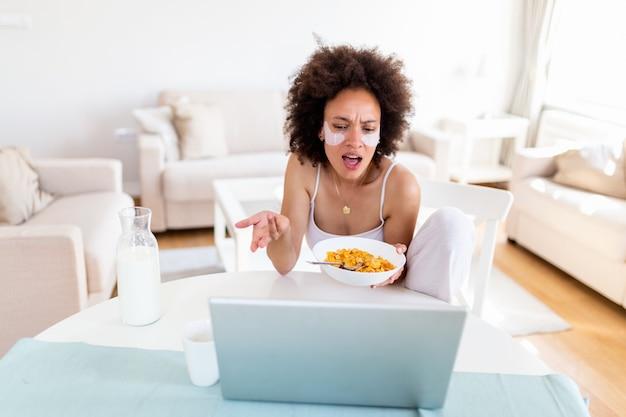 Immagine della giovane donna felice che si siede all'interno al tavolo con i fiocchi di mais della tenuta del computer portatile.