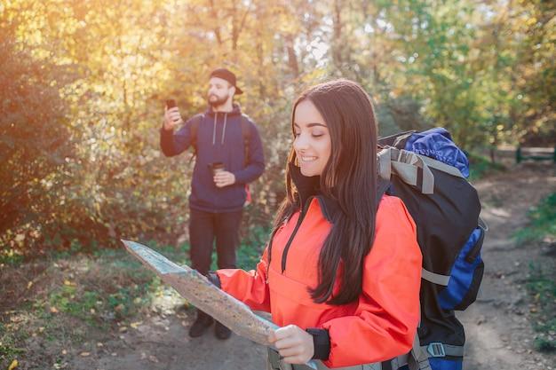 Immagine della giovane donna sicura e allegra con bakcpack. tiene la mappa e la guarda. il giovane dietro prova a catturare il segnale sul telefono. lo regge.