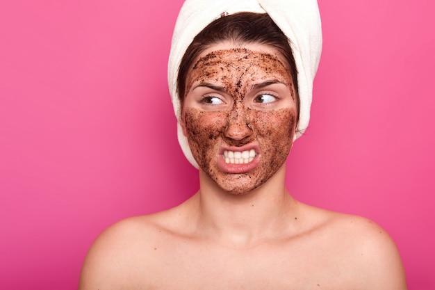 Immagine della giovane modella attraente infastidita con un asciugamano bianco sulla bocca che apre la testa, mettendo i denti, guardando da parte, avendo un'espressione del viso irritata. concetto di cura della pelle, bellezza e trattamento.