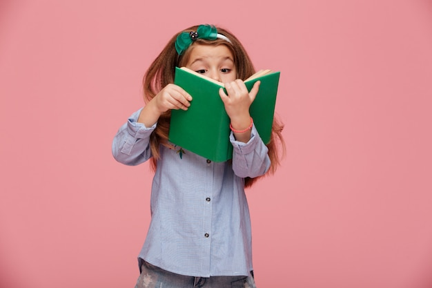 Immagine della ragazza divertente con capelli ramati lunghi che legge divertiresi interessante del libro