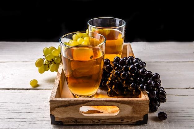 Immagine della scatola di legno con due bicchieri di vino, uva nera e verde
