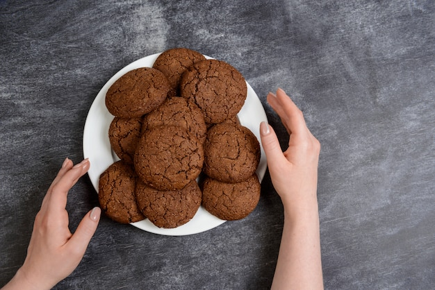 Immagine delle mani che tengono i biscotti del cioccolato sopra superficie di legno