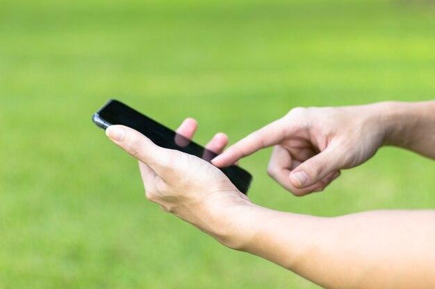 Immagine delle mani maschile utilizzando smartphone nero nel parco