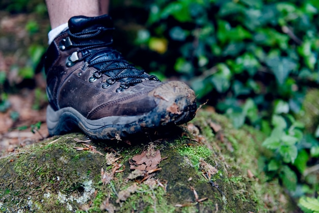 Immagine delle scarpe sporche dell'uomo che stanno sulla roccia