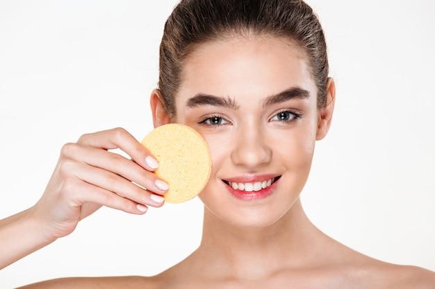 Immagine di attraente donna dai capelli scuri con morbida pelle sana che stende il trucco con una spugna cosmetica