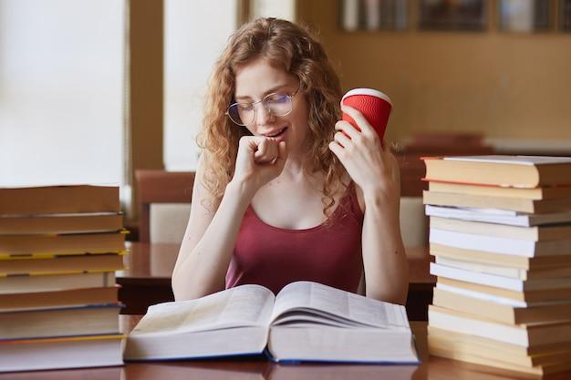 Immagine di attraente studente assonnato seduto nella sala di lettura e sbadiglio, preparazione per le lezioni, lavoro straordinario, sembra stanco, bevendo caffè, femmina dai capelli sexy legge l'enciclopedia, trovando informazioni.