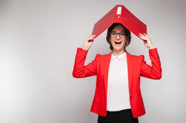 Immagine di bella donna in giacca rossa in piedi e scherzare con i documenti