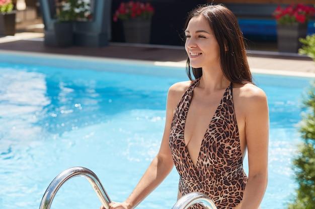 Immagine di bello modello positivo che posa in acqua pulita, che esce dalla piscina, che ottiene piacere dalle sue vacanze estive, che sorride sinceramente, toccando le scale con entrambe le mani.
