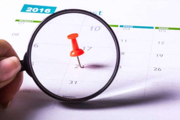 Immagine di concetto di un calendario con puntina rossa