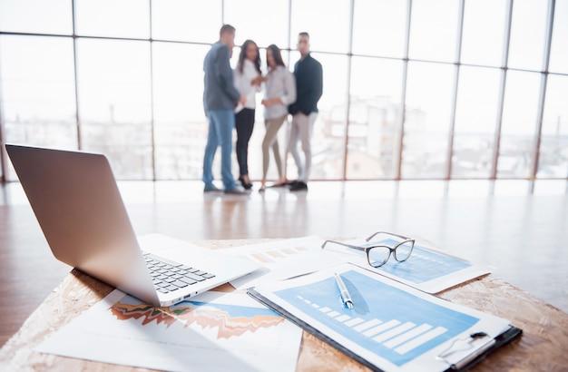 Immagine di documenti aziendali sul posto di lavoro con i partner che interagiscono sullo sfondo. concetto di lavoro di squadra