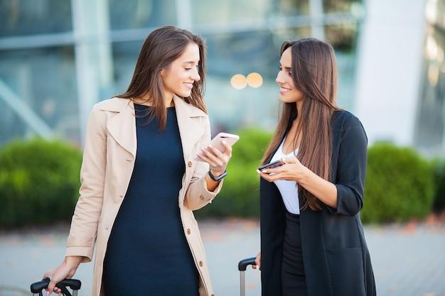 Immagine di due donne europee gioiose guardando smartphone, mentre in piedi con i bagagli vicino all'aeroporto in attesa di volo o dopo la partenza. trasporto aereo