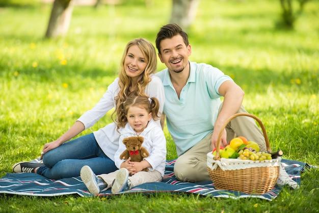 Immagine di felice giovane famiglia avendo picnic all'aperto.