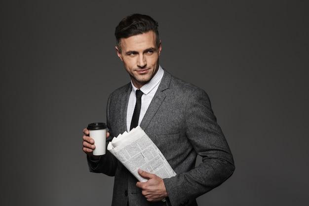 Immagine di fiducioso uomo bruna vestito in costume di affari che osserva da parte con caffè da asporto e giornale in mano, isolato sopra il muro grigio